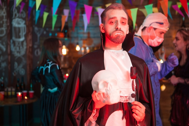 Portrait of dracula holding a human skull celebrating halloween with his monster friends. scary doctor covered in blood in the background.