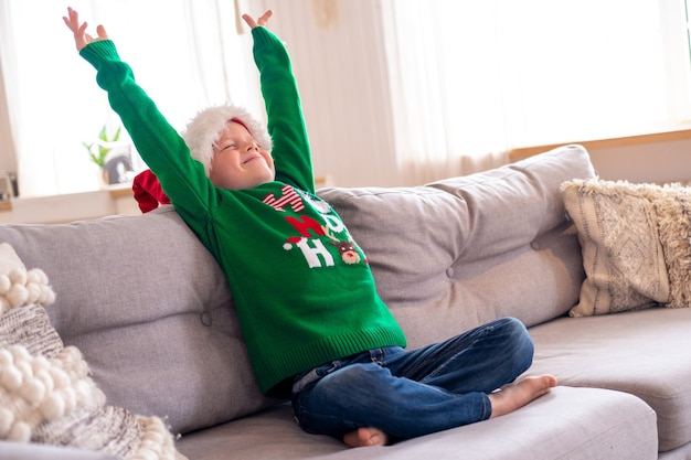 Portrait dreaming boy with closed eyes in santa hat and christmas costume sitting at home hands up