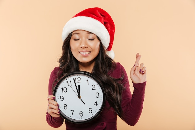 Portrait of dreaming girl in santa claus red hat holding clock showing nearly 12 making wish with fingers crossed over peach background