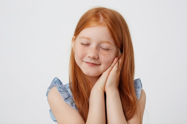 Portrait of dreaming little freckles red-haired girl in blue dress, looks sleppy, with folded palms at the cheeks, stands over white background.