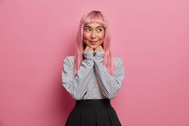 Ritratto di donna asiatica sognante con i capelli rosa, tiene le mani sotto il mento, guarda pensieroso, cerca di immaginare qualcosa di positivo