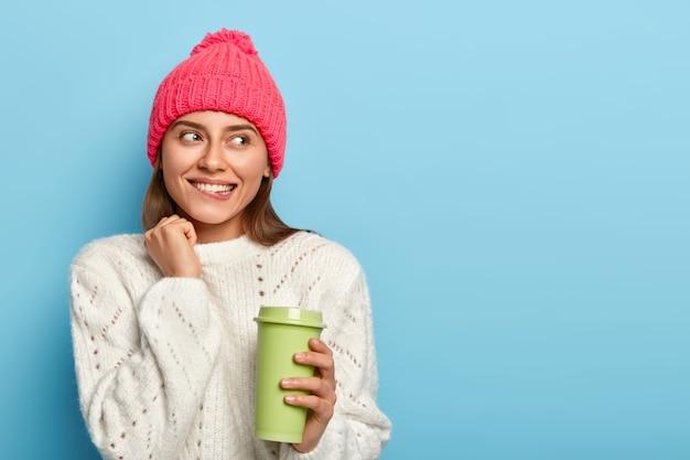 Ritratto di bella donna sognante guarda da parte, morde le labbra, tiene la tazza di caffè, vede qualcosa di allettante, indossa un cappello rosa e un maglione bianco