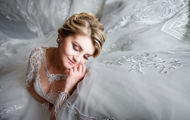Portrait of dreamy blonde bride posing in a luxury room before the ceremony