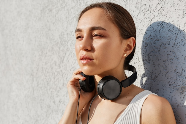 Portrait of dreamy brunette woman wearing white top and having headphones over neck, looking away with pensive facial expression, posing against grey wall outdoor.