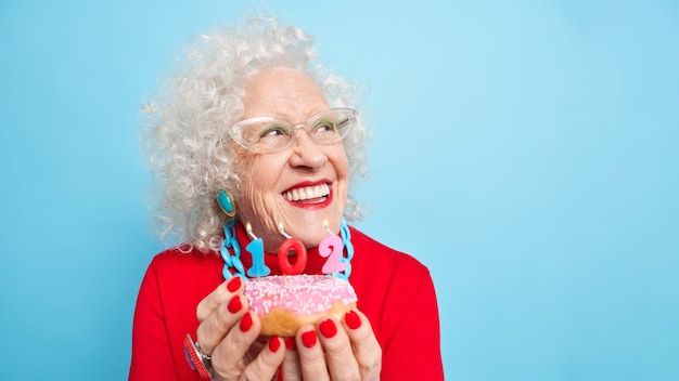 Portrait of dreamy cheerful curly elderly woman smiles broadly concentrated aside thinks about wish before blowing candles wears red jumper jewelery bright makeup holds tasty glazed doughnut