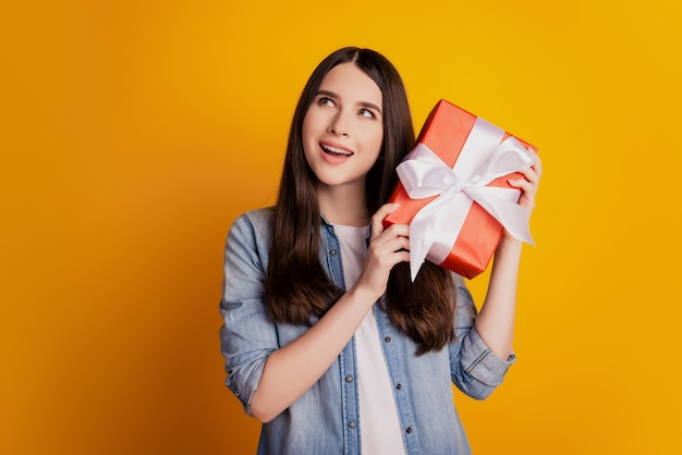 Portrait of dreamy curious girl hold present box guessing look empty space on yellow background