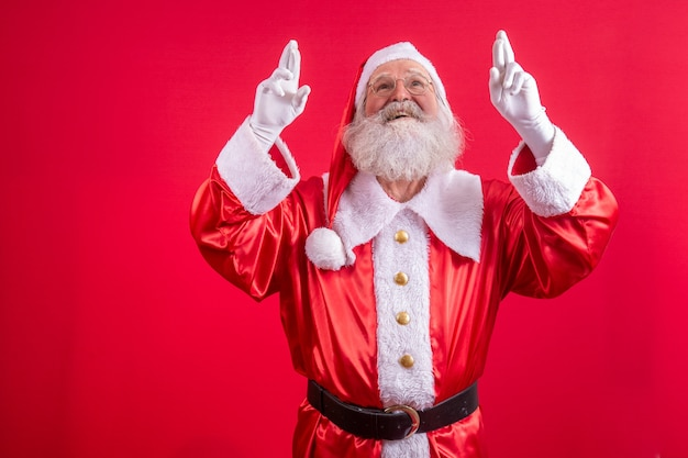 Portrait of dreamy elderly man in santa claus costume  crossing fingers making a wish, christmas magic, winter holidays. indoor studio shot isolated on red background