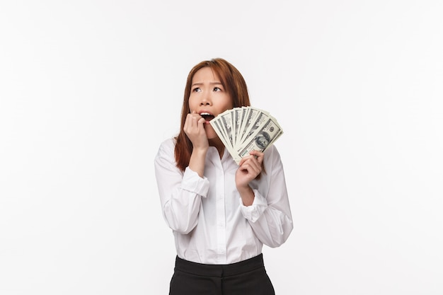 Portrait of dreamy and excited young happy woman biting her fingers and looking up as dream came true, holding fan of cash, become rich and think how she fulfill her dreams,