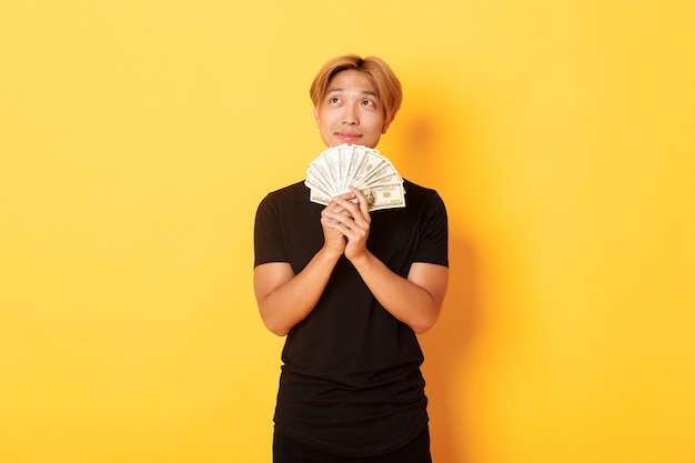 Portrait of dreamy handsome asian guy showing his savings and thinking, looking upper left corner, holding money, standing yellow wall