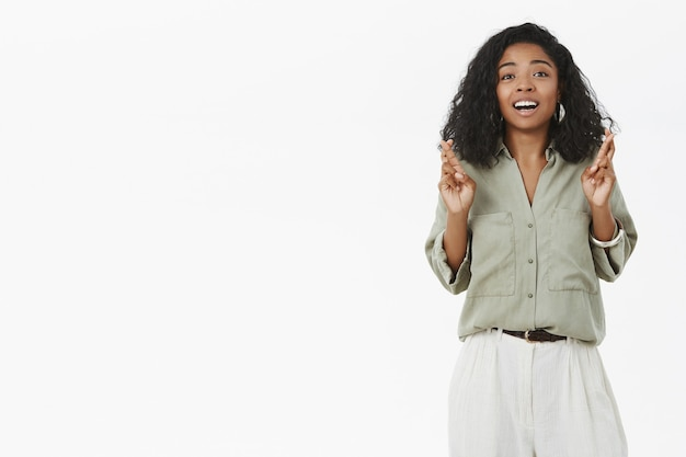 Portrait of dreamy and hopeful charming dark-skinned woman with curly hairstyle crossing fingers