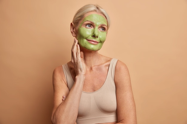 Portrait of dreamy middle aged woman applies green mask on face stands thoughtfully and looks away undergoes beauty procedures dressed casually isolated over beige wall