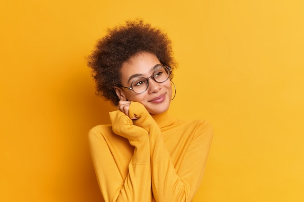 Portrait of dreamy twenty years old female keeps hands near face and has romantic expression has curly bushy hair wears spectacles turtleneck.