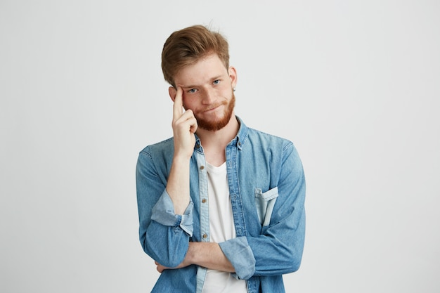 Portrait of dreamy young man thinking with hand on cheek.