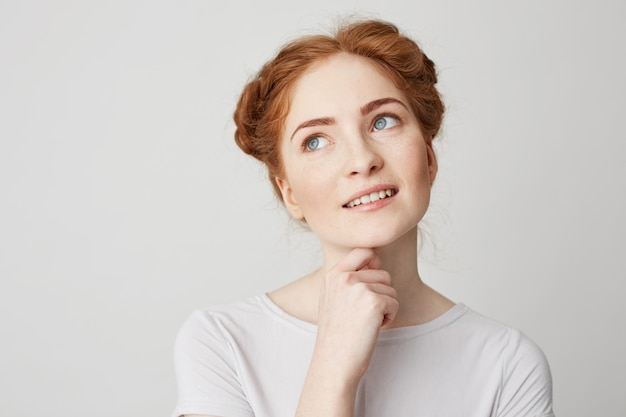 Portrait of dreamy young pretty girl with red hair thinking dreaming touching chin .