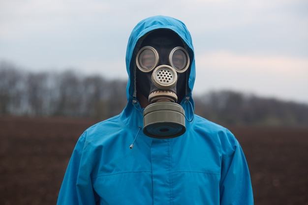Portrait of ecologist working outdoors, wearing gas mask and uniform, scientist explores surroundings, scientist works in open air
