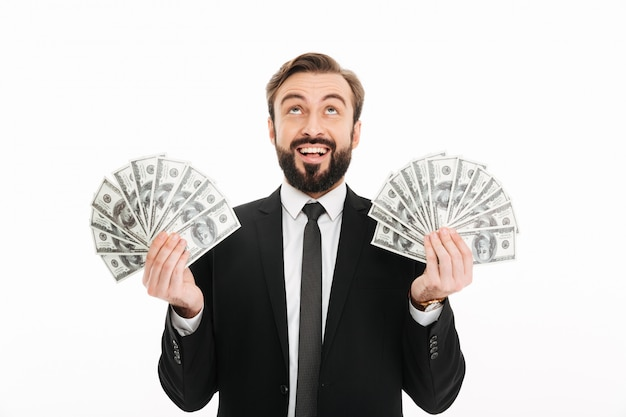 Portrait of ecstatic businessman holding two fans of money dollar cash and looking upward, isolated over white wall