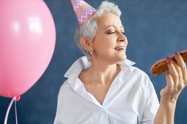 Ritratto di signora in pensione felice estatica in elegante camicia bianca e cappello a cono ballare musica alla festa di compleanno, tenendo in mano un palloncino rosa elio.