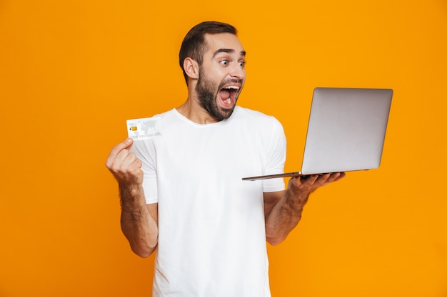 Portrait of ecstatic man 30s in white t-shirt holding silver laptop and credit card, isolated