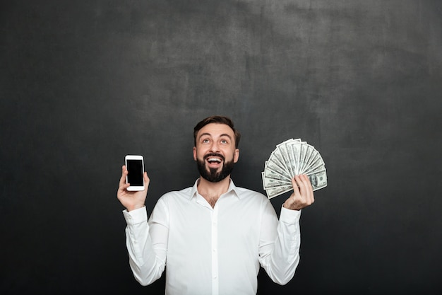 Portrait of ecstatic man expressing online earnings with holding lots of money dollar currency and smartphone, isolated over dark gray