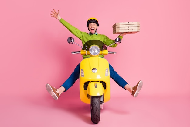 Portrait of ecstatic overjoyed guy driving moped bringing pizza