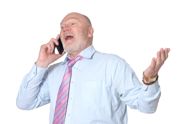 Portrait of elderly  businessman with mobile phone on background