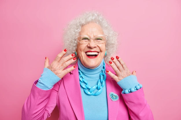 Portrait of elderly curly haired woman raises hands smiles broadly wears spectacles fashionable outfit necklace being in good mood
