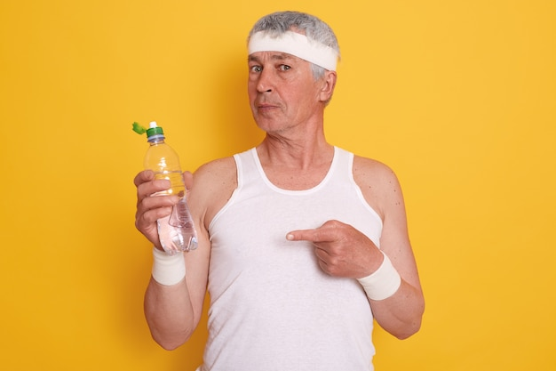 Portrait of elderly male wearing casual sleeveless t shirt and headband, holding bottle of water and pointing at it with his index finger