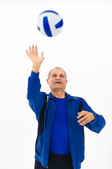 Portrait of an elderly man in a blue tracksuit playing with a ball on white