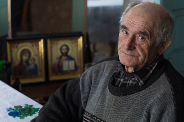 Portrait of an elderly man. grandfather sits in his room in the background of the icons.