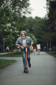 Portrait of elderly man with kick scooter in a summer park