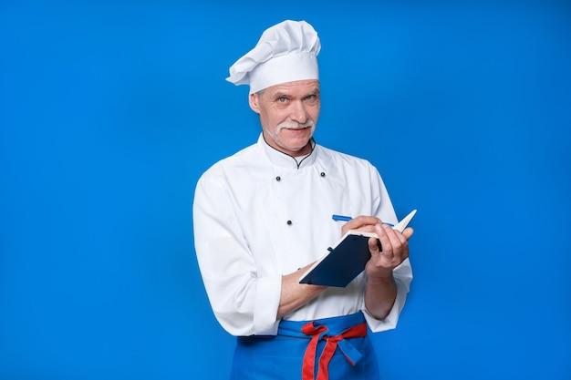 Ritratto di anziano chef isolato sulla parete blu, con il suo blocco note, scrivere una nuova ricetta.