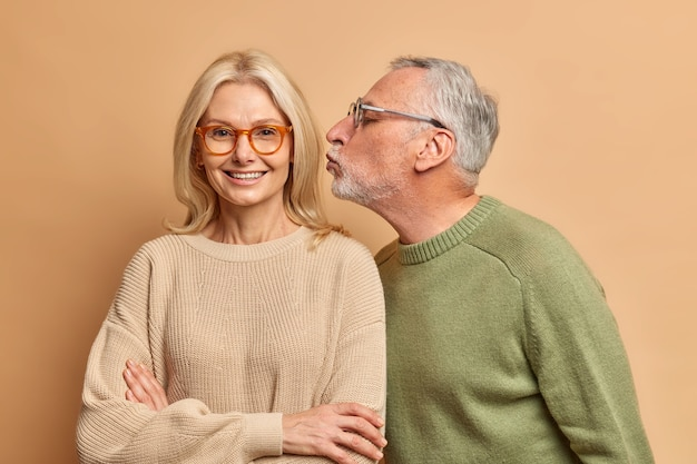 Portrait of elderly woman gets affectionate kiss from husband have good relationship dressed on casual sweaters isolated over brown wall