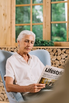 Portrait of an elderly woman sitting on chair reading newspaper