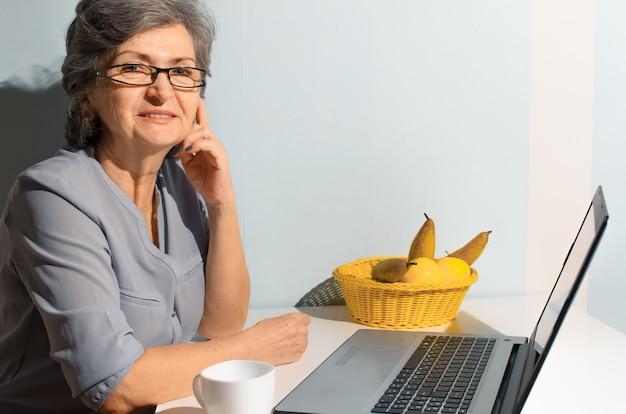 Портрет пожилой женщины с помощью ноутбука дома. старшая женщина улыбается