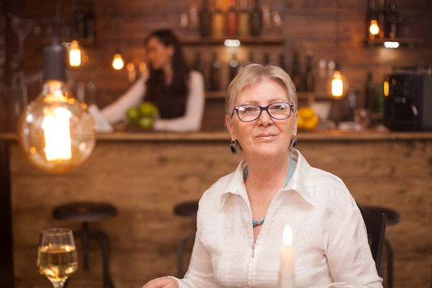 Portrait of elderly woman in a vintage restaurant. a glass of white wine. blurred barmaid working in the background.
