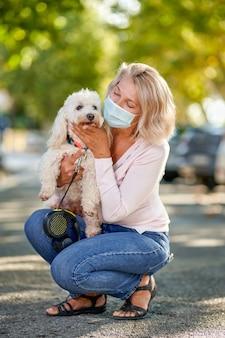 Портрет пожилой женщины с собакой на открытом воздухе в антивирусной маске