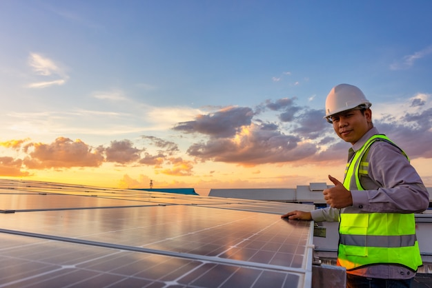 Portrait of electrician in safety helmet and uniform on background rooftop of photovoltaic solar panels. male technician at solar station.