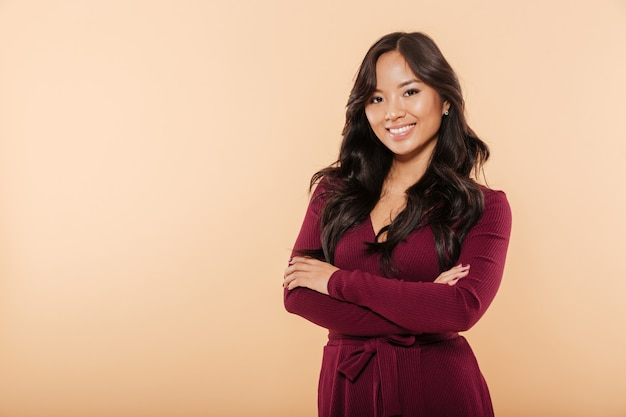 Portrait of elegant asian female in pretty maroon dress posing on camera with arms folded isolated over peach background
