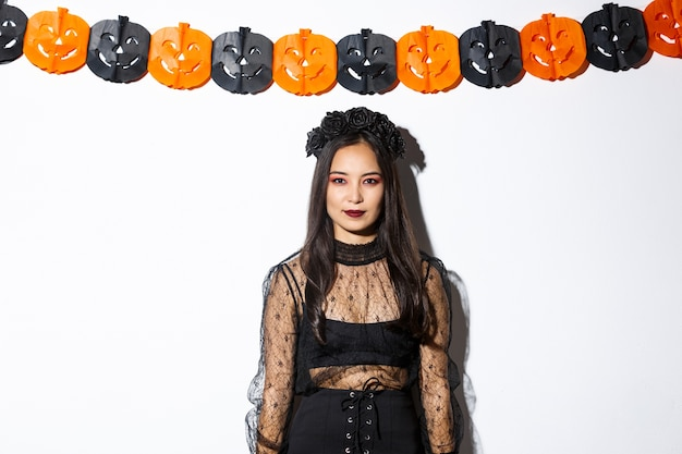 Portrait of elegant asian woman in witch costume, looking confident and standing against pumpkin streamers, decorations for halloween over white background.