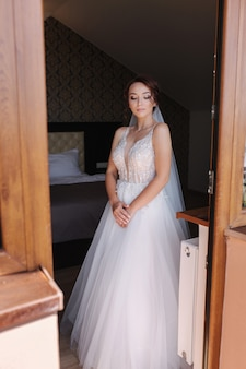 Portrait of elegant bride in fashion wedding dress stand on the balcony and posing