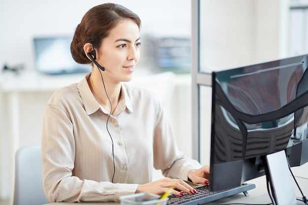 Portrait of elegant businesswoman wearing headset while using computer at desk in office