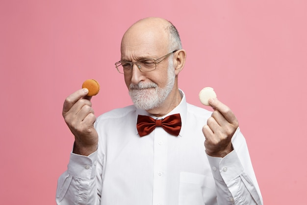 Portrait of elegant elderly european man with thick beard holding two tiny macarons in both hands, looking at them, deciding which of cookie to eat first, having doubtful confused facial expression