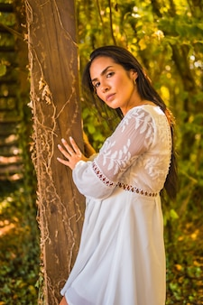 Portrait of an elegant hispanic female wearing a white dress and posing leaning on the tree