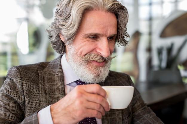 Ritratto del maschio elegante che gode del caffè