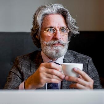 Ritratto di elegante maschio maturo tenendo la tazza di caffè