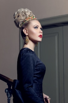 Portrait of an elegant model in black dress, with evening makeup, next to staircase