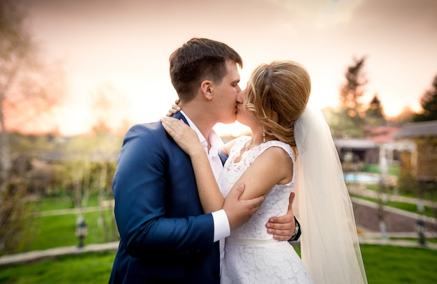 Portrait of elegant newly married couple kissing in park at sunset