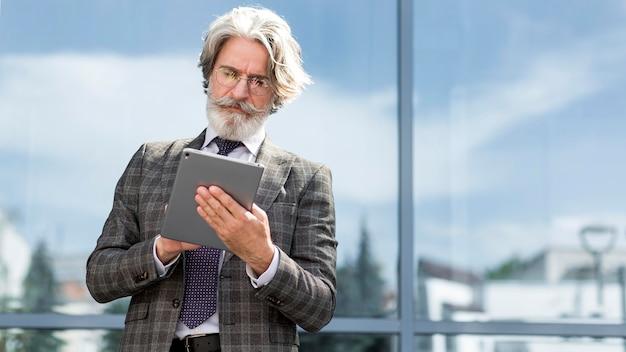 Ritratto del tablet di navigazione maschile senior elegante