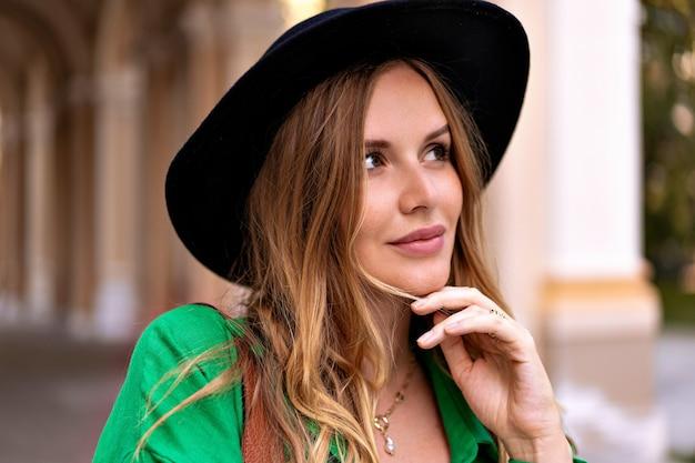 Ritratto di donna alla moda elegante con capelli biondi ricci lentiggini viso e trucco naturale, indossando fedora nera in posa per strada.