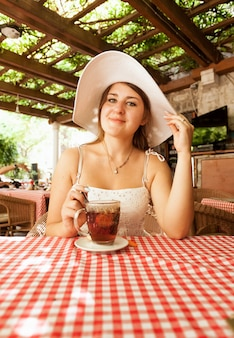 Portrait of elegant woman sitting with cup of tea at cafe